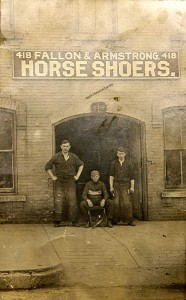 Clarence Armstrong stands left, in front of his blacksmithing business